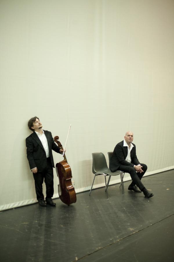 Friedrich Kleinhapl lehtn an der Wand und hält sein Chello in der Hand; der Pianist Andreas Woyke sitzt auf einem Sessel danmeben