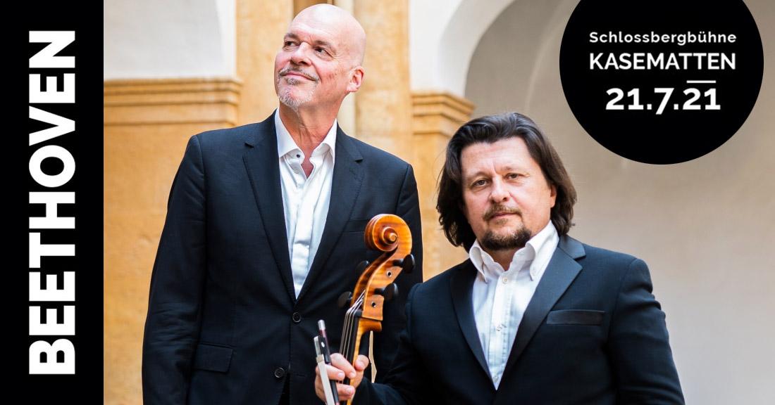 Der Cellist Freidrich Kleinhapl und der Pianist Andreas Woyke stehen in einem Innenhof und blicken in die Kamera